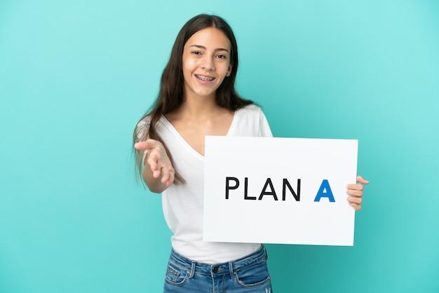 Młoda francuzka odizolowana na niebieskim tle trzymająca tabliczkę z napisem plan a making deal
