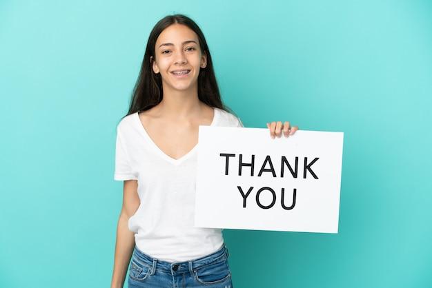 Młoda francuzka odizolowana na niebieskim tle trzymająca tabliczkę z tekstem dziękuję ze szczęśliwym wyrazem twarzy