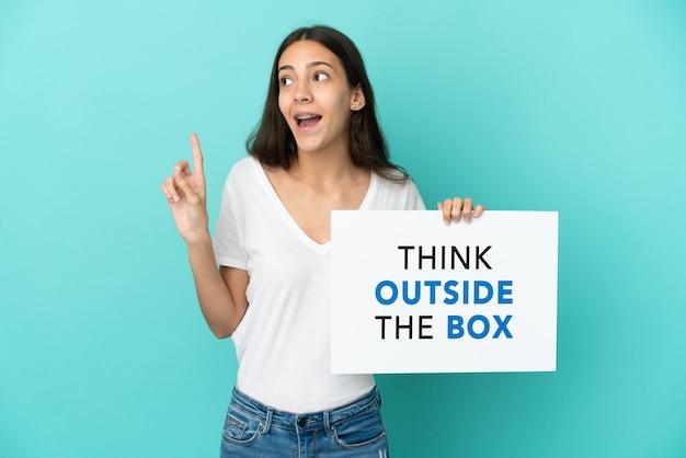 Młoda francuzka odizolowana na niebieskim tle trzymająca tabliczkę z tekstem think outside the box and thinking