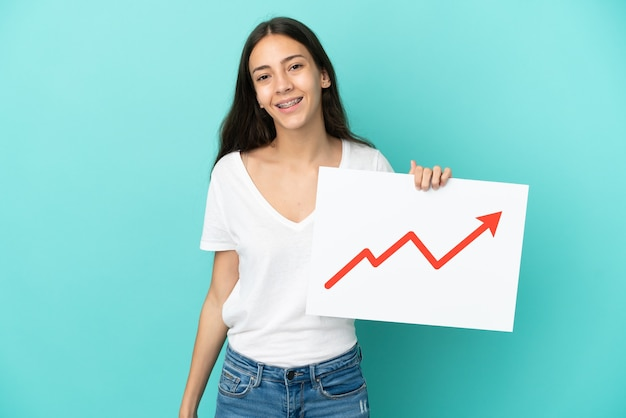 Młoda francuzka odizolowana na niebieskim tle trzymająca znak z rosnącym symbolem strzałki statystyki z radosnym wyrazem twarzy