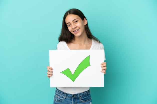 Młoda francuzka samodzielnie na niebieskim tle trzyma tabliczkę z tekstem ikona zielonego znacznika wyboru z happy wypowiedzi