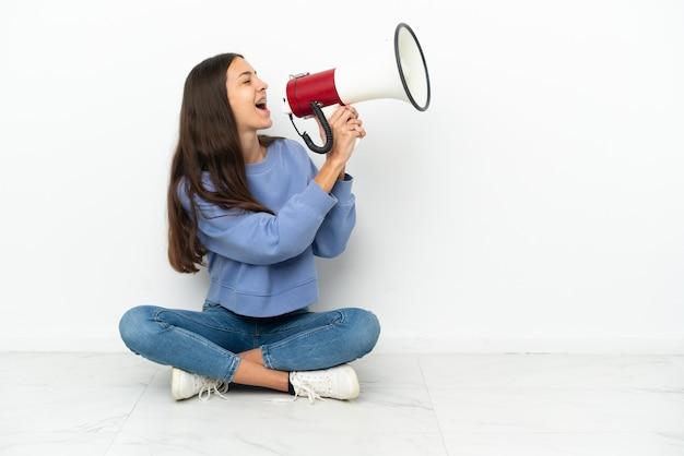 Młoda Francuzka Siedzi Na Podłodze I Krzyczy Przez Megafon Premium Zdjęcia