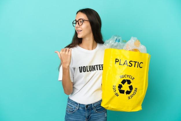 Młoda francuzka trzyma torbę pełną plastikowych butelek do recyklingu, wskazując na bok, aby przedstawić produkt
