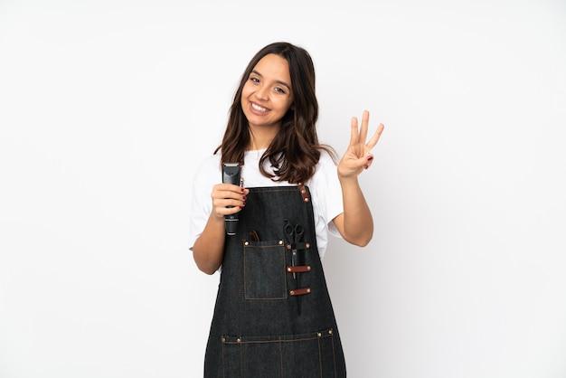 Młoda fryzjer kobieta na białej ścianie szczęśliwy i licząc trzy z palcami