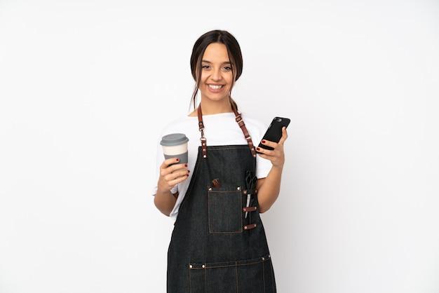 Młoda fryzjer kobieta na białej trzyma kawę zabrać i wiszącą ozdobę