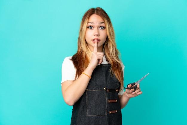Młoda fryzjerka na odosobnionym niebieskim tle pokazującym znak ciszy gest wkładania palca do ust