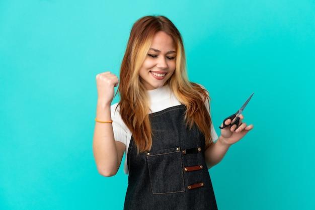Młoda fryzjerka na odosobnionym niebieskim tle świętuje zwycięstwo