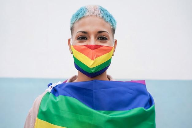 Młoda gejowska kobieta ubrana w tęczową flagę lgbt na zewnątrz podczas parady dumy