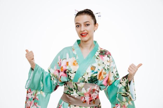 Młoda gejsza kobieta w tradycyjnym japońskim kimonie patrząca z przodu szczęśliwa i pozytywnie pokazująca kciuki do góry stojąca nad białą ścianą