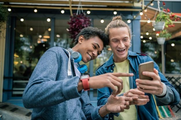 Młoda generacja. pozytywnie zachwyceni panowie patrząc na smartfona, ciesząc się nowymi technologiami