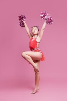 Młoda gimnastyczka dziewczyna cheerleaderka robi ćwiczenia