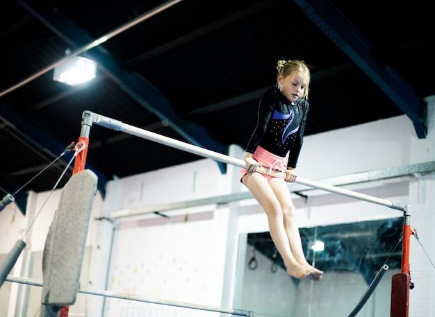 Młoda gimnastyczka na poziomym pasku