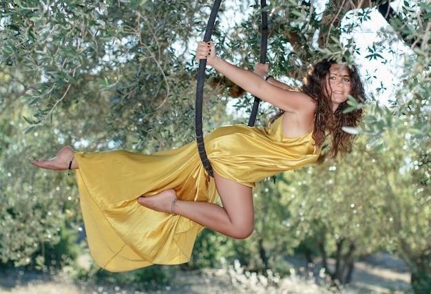 Młoda gimnastyczka pozuje na kole z lotu ptaka przed ogrodem drzew oliwnych