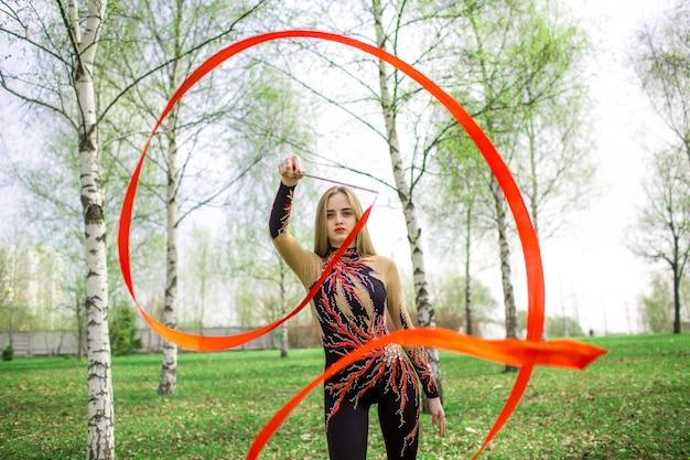 Młoda gimnastyczki dziewczyna z czerwoną wstążką robi rytmiczne gimnastyki w parku