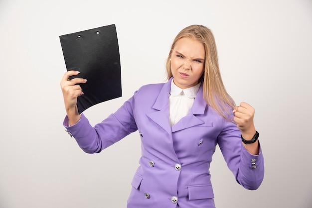 Młoda gniewna kobieta z ołówkiem i tabletem na białym.