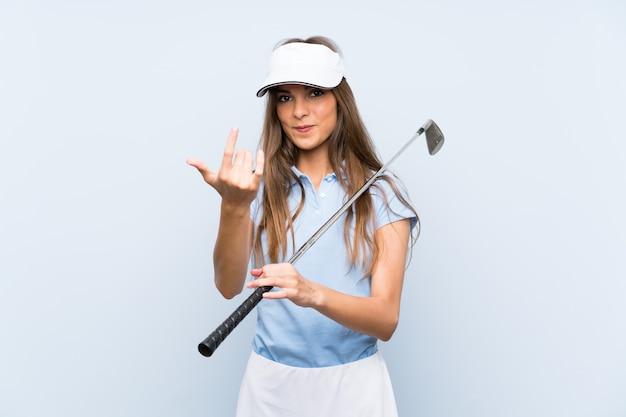 Młoda golfista kobieta nad odosobnioną błękit ścianą zaprasza przychodzić z ręką. cieszę się, że przyszedłeś