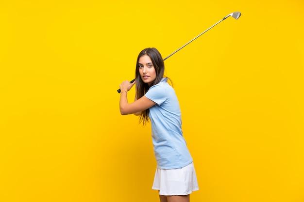 Młoda golfista kobieta nad odosobnioną kolor żółty ścianą