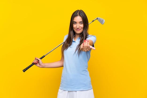 Młoda golfista kobieta zaprasza przychodzić z ręką. szczęśliwy, że przyszedłeś