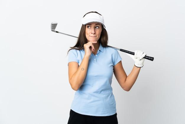 Młoda golfistka na białym tle, mająca wątpliwości i myśląca