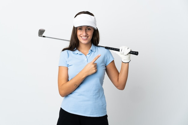Młoda golfistka na białym tle wskazuje na bok, aby zaprezentować produkt