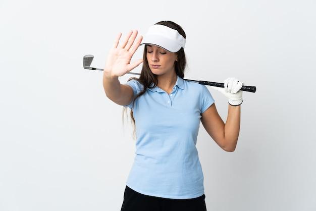Młoda golfistka na na białym tle robi gest zatrzymania i rozczarowana