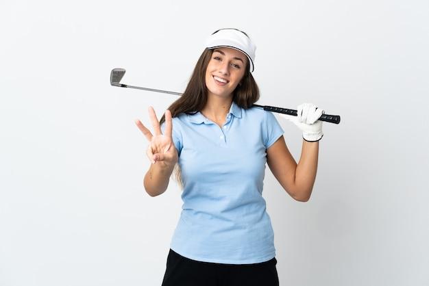 Młoda golfistka na odosobnionym białym tle szczęśliwa i licząca trzy palcami