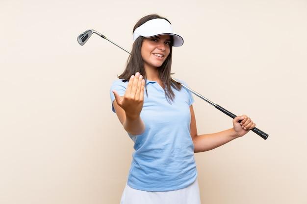 Młoda golfistka ponad odosobnioną ścianą zapraszająca do ręki, szczęśliwa, że przyszłaś
