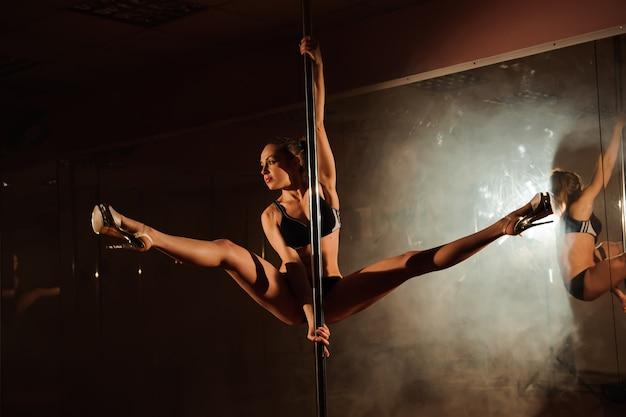 Młoda gorąca kobieta w seksownej bieliźnie wykonuje zmysłowy taniec na rurze.