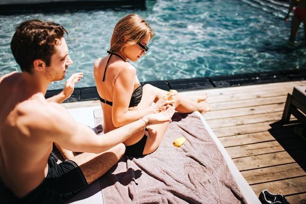 Młoda gorąca para odpoczywa w swimpool. facet siedzi za dziewczyną i używa kremu przeciwsłonecznego na skórę pleców. używa go przed opalaniem. dziewczyna siada przed nim i opiekuje się swoim ciałem.