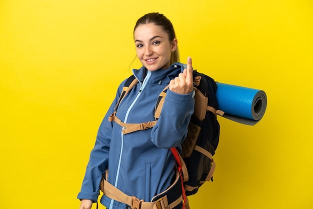 Młoda góralka z dużym plecakiem na odosobnionym żółtym tle robi nadchodzący gest