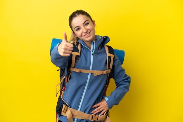 Młoda góralka z dużym plecakiem na odosobnionym żółtym tle z kciukami do góry, ponieważ stało się coś dobrego