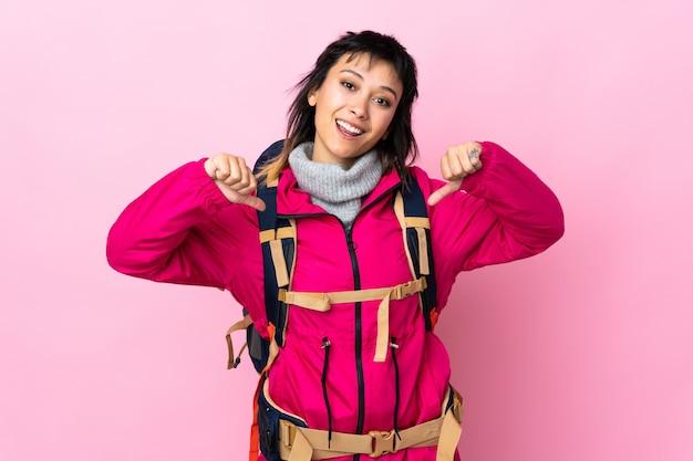 Młoda góralska dziewczyna z dużym plecakiem na różowej ścianie dumna i zadowolona z siebie