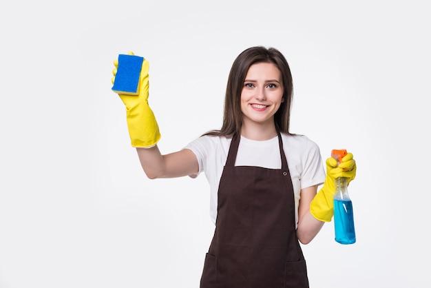 Młoda gospodyni domowa czyszczenia dywanem i detergentem na białym tle