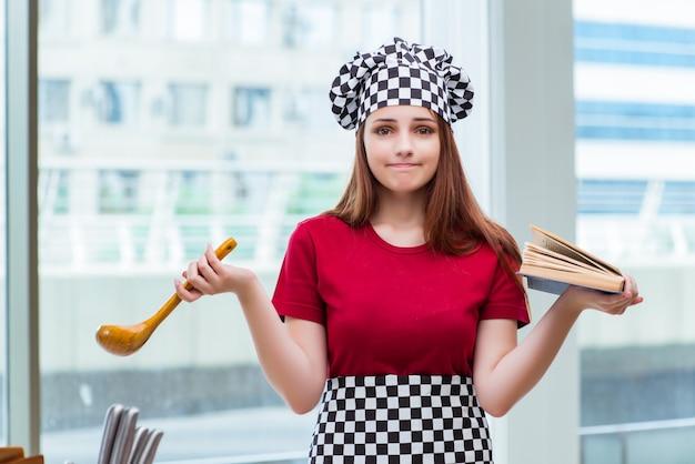 Młoda gospodyni domowa odnosząca się do książki kucharskiej