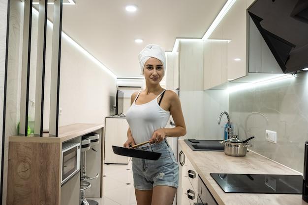 Młoda gospodyni domowa po prysznicu zawinięta w biały ręcznik stoi w kuchni i przygotowuje śniadanie w rondlu