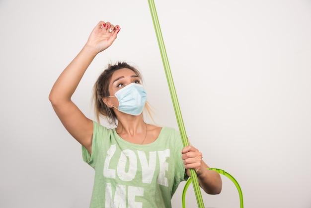 Młoda gospodyni domowa trzyma mop na białej ścianie z maską na twarz.