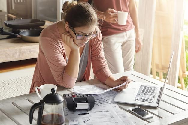 Młoda gospodyni domowa ubrana niedbale skupiona na papierkowej robocie