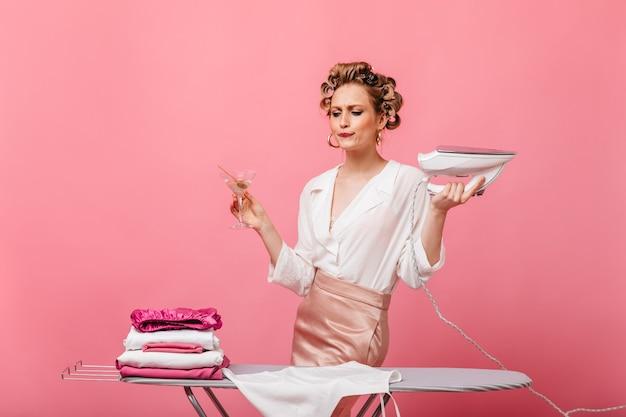 Młoda gospodyni domowa w eleganckim stroju z żelazkiem i martini na różowej ścianie
