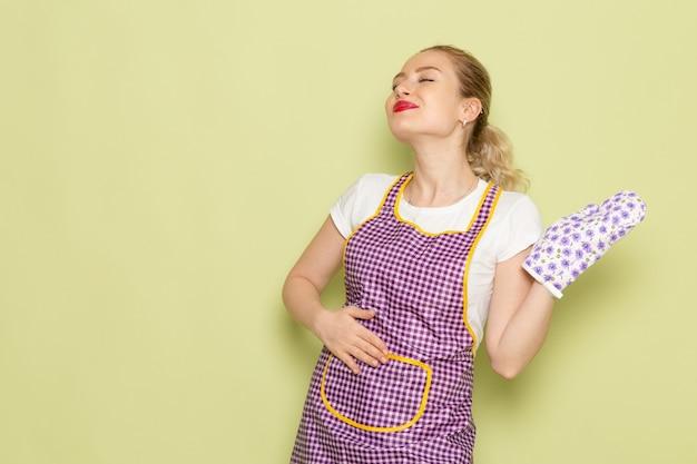 Młoda gospodyni domowa w koszuli i fioletowej pelerynie pozowanie na zielono