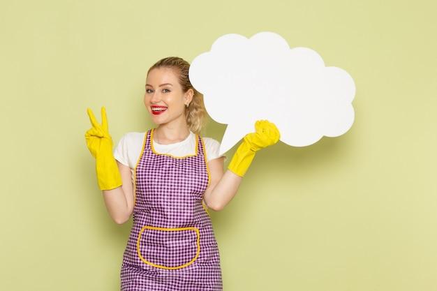 Młoda gospodyni domowa w koszuli i fioletowej pelerynie z żółtymi rękawiczkami trzyma duży biały znak na zielono