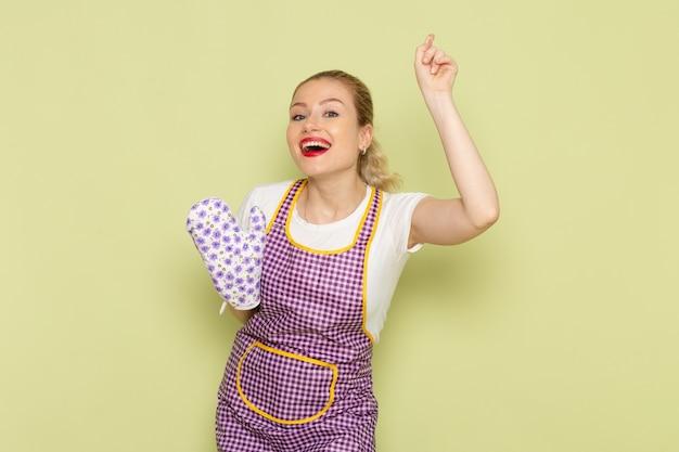 Młoda gospodyni domowa w koszuli i kolorowej pelerynie stoi i pozuje z uśmiechem na zielono