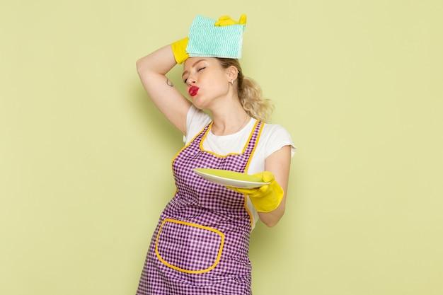 Młoda gospodyni domowa w koszuli i kolorowej pelerynie suszenia płyty z żółtymi rękawiczkami na zielono