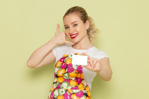 Młoda gospodyni domowa w koszuli i kolorowej pelerynie trzymając białą kartę z uśmiechem na zielono