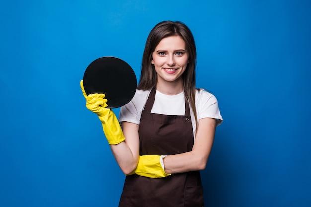 Młoda gospodyni domowa w rękawiczkach pokazując gąbkę i czysty talerz na białym tle