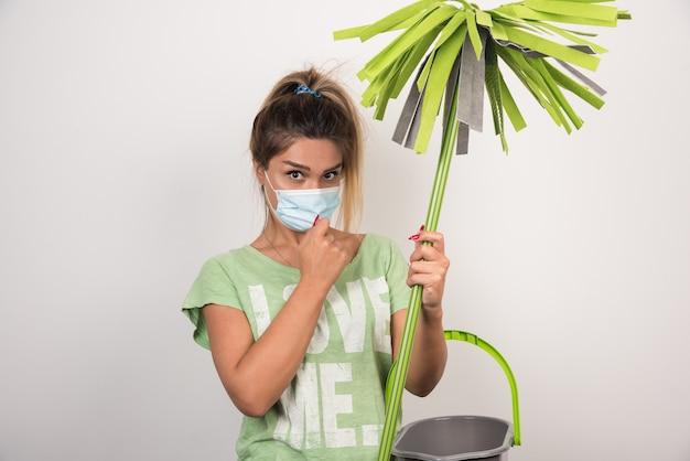 Młoda gospodyni domowa z mopem trzymając maskę na twarzy i patrząc z przodu na białej ścianie.