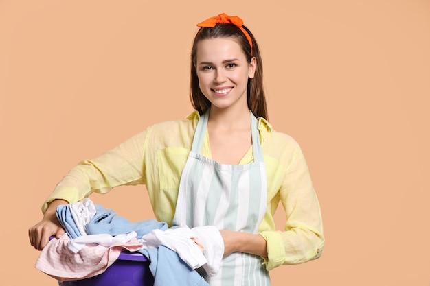 Młoda gospodyni domowa z praniem na beżu
