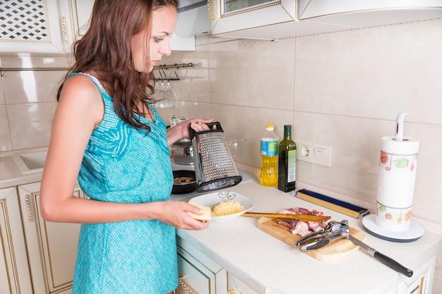 Młoda gospodyni gotuje wieczorny posiłek stojąc przy kuchennym blacie tłukąc ser cheddar, aby dodać do talerza surowego mięsa stojącego gotowego do gotowania