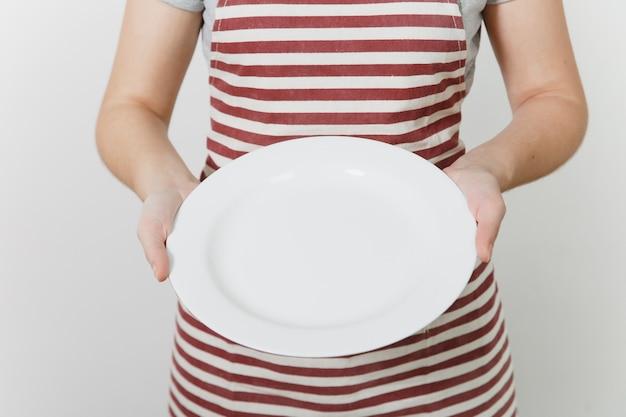 Młoda gospodyni kaukaski w pasiasty fartuch, szary t-shirt na białym tle. kobieta gospodyni trzymająca w rękach biały pusty okrągły talerz