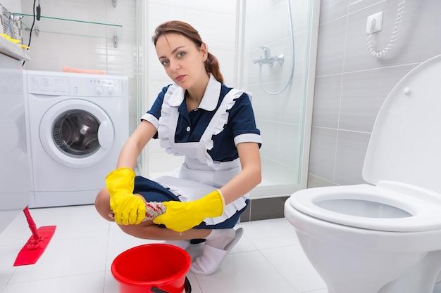 Młoda gospodyni lub pokojówka czyszcząca podłogę klęcząca obok kolorowego czerwonego wiadra wykręcająca szmatkę z mopa i patrząca w kamerę