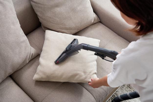 Młoda gospodyni sprzątająca sofę za pomocą odkurzacza w salonie